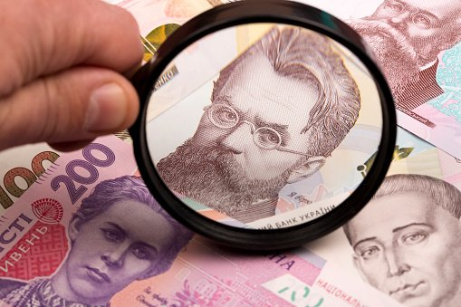 Ukrainian hryvnia in a magnifying glass a business background