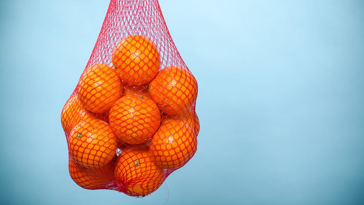 Mesh bag of fresh oranges healthy tropical fruits from supermarket on blue. Food retail.; Shutterstock ID 222216166