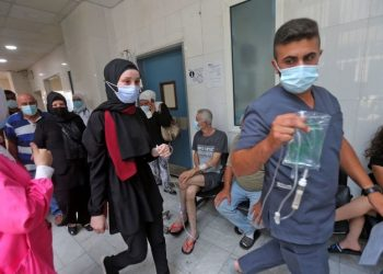 A medic assists a patient as others wait in a hallway at the Rafic Hariri University Hospital (RHUH) in Lebanon's capital Beirut on July 23, 2021. - Lebanon's crashing economy has piled pressure on hospitals, leaving them increasingly ill-equipped to face any new wave of the novel coronavirus, a top hospital director has warned. (Photo by STR / AFP) (Photo by STR/AFP via Getty Images)