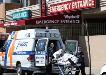 NEW YORK, USA - APRIL 06: Healthcare workers help a patient at the Wyckoff Heights Medical Center in Brooklyn, New York City, United States on April 6, 2020. New York Gov. Andrew Cuomo said that of the confirmed 130,689 coronavirus (Covid-19) infections state has recorded 4,758 people have died, up from 4,159 recorded on Sunday.  ( Tayfun Coşkun - Anadolu Agency )